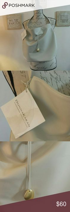 Donna karan. Bag brand new Very soft almost like soft leather was a gift . With make up .... great steal ..... so cute brand new with tag great bag very elegant Bags