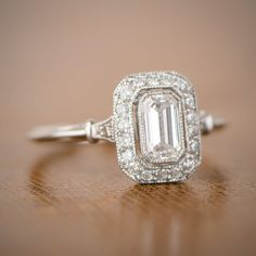 WOW! A stunning emerald cut diamond surrounded by a halo of round diamonds. The triple wire adds to the delicacy of the ring.