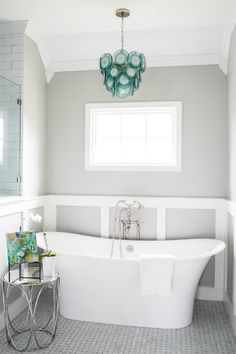Aqua blue and gray bathroom features a blue glass chandelier, Regina Andrew Mini Diva Aqua Chandelier, over a freestanding tub and a satin nickel vintage style tub filler surrounded white white and gray paneled walls.