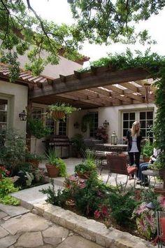 Terrasse Stein mit bepflanzter Pergola und Terrassenbeeten