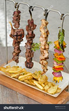 Cooked Chicken, Beef And Vegetable Kebab Skewers Hanging From A Rack, Served With Fries, And Ready To Eat. Стоковые фотографии 384391996 : Shutterstock
