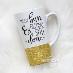 """Featured here is our Messy Bunmug. This mug reads """"Messy bun & getting shit done"""". The print is professionally printed on the mug in black. If you would like a different color print, please leave us a note in the """"Additional Notes"""" section.  Choose from anyfourof our available mug styles. With several glitter options, you can also add a little extra shine to your custom mug!Thetextured glitter dipped bottom is sealed and will not flake off in your hands.  Every mug is handmade and…"""