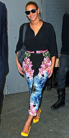 BEYONCÉ  The new mom adds a pop of blue to her belted floral-patterned jumpsuit, which she pairs with bright yellow pumps.