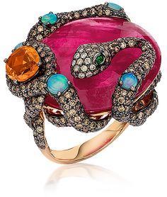 Cellini Jewelers, Wendy Yue Ruby Snake Ring This exquisite Wendy Yue ring showcases the designers admiration of natures. Brown and white diamond pavé snake, accented with opals, curls around a faceted round ruby, and oval orangy-yellow sapphire; in 18-karat rose gold. Brown and White Diamond weight: approximately 4.34 carats total; Rose-cut Ruby weight: 23.58 carats; Yellow Sapphire weight: 1.51 carats; Tsavorite weight: 0.03 carat .