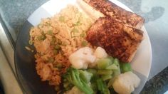 Chili powder crusted salmon, with yellow rice and green peas with broccoli and cauliflower.