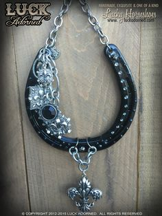 """DECATUR STREET"" is a glossy black horseshoe with a fun, New Orleans vibe. Fleur de lys pendants hang from big, bold and chunky silver chain. Hand placed Swarovski crystals in black diamond are featur"