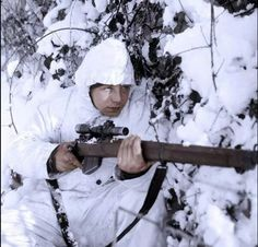 A 6th Airborne Division sniper on patrol in the Ardennes, wearing a snow camouflage suit and using a Lee Enfield No. 4 Mk.1, 14 January 1945.