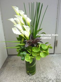 Floral arrangement using lilies and grasses. Add interest by wrapping a leaf around the base of the stems inside the arrangement,