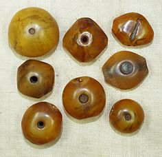 These diamond-shaped amber beads are over 100 years old and are found in Mauritania and Niger. They are an imitation (like Bakelite) amber made in Germany from plant resin. Hole is approximately 1.5-2mm and has a decorative hole through the center,