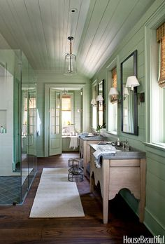 Designed to feel like an enclosed porch, this vintage-feeling bathroom designed by Bill Ingram in Lake Martin, Alabama, features lantern-style light fixtures, hidden medicine cabinets, and freestanding, antique oak washstands.