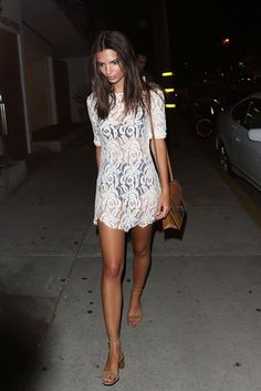 Emily Ratajkowski wears a sheer lace dress with nude lace-up heels and a tan leather shoulder bag