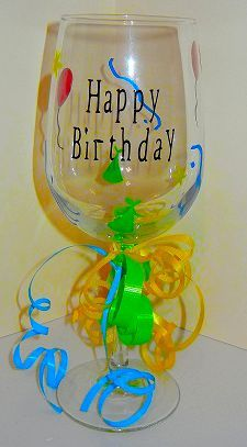 """""""Happy Birthday"""" wine glass.  Decorated with red balloons, blue streamers, green party hats and yellow stars.  Contact www.annieks.com to purchase this glass or create your own.  Can change colors and design."""
