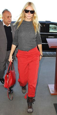 Gwyneth Paltrow wore a pair of bright red Band of Outsiders x Goop trousers that coordinated with her Valentino handbag on her way to catch a flight at LAX. A gray ribbed sweater, brown combat boots, and sunnies finished off the look. #InStyle
