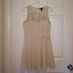 Forever 21 cream bow dress Gorgeous cream dress w/ a bow and lace detail. Only wore once but someone burnt me with the cigarette so there is a small spot shown in the photo. It isn't noticeable, and the bottom is lined that that wasn't harmed. Forever 21 Dresses