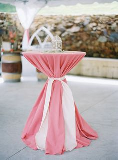 reception wedding ideas: pink floor length table cloth with white sash