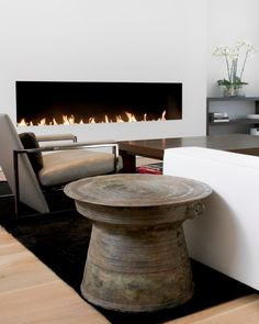 Minimalist fireplace with simple furniture. Love these rain drums used as side tables -- we have one in our living room~ place it in the covered outdoor room
