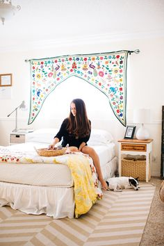 """The master bedroom: it's still always a work in progress, but the way the late afternoon light comes in over the bed is absolutely perfect. When I'm in the kitchen, my bed is my office. A calm and cozy space for me to work in. The tapestry above my bed is one of my most asked-about pieces. It's a one-of-a-kind, hand stitched vintage piece. I love it through all its imperfections and bleeding inks."""