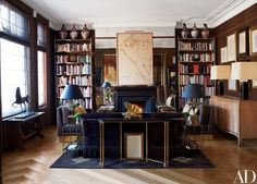 The drawing room features a work on paper by Jean Cocteau over the mantel, a pair of brass bookshelves custom made after a Billy Baldwin design for Cole Porter, a vintage console by Jansen, and a sofa by Moschino's firm, Nicholas Haslam Ltd | archdigest.com