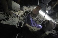 Week of May 17-23, 2014 Residents try to pull a man out from under rubble at the site of an alleged missile attack in Mareh, Syria, on Monday. Jalal Al-Mamo/Reuters