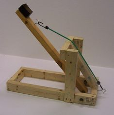Helped my student make this catapult for a high school physics project. Used scrap lumber, screws, 2 cup hooks, and a short bungee cord. Things To Make Out Of Scrap Wood Kids Woodworking Projects, Woodworking Workbench, Woodworking Furniture, Woodworking Shop, Intarsia Woodworking, School Projects, Fun Projects, Wood Projects, Garden Projects