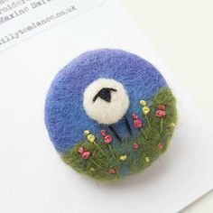 An original hand crafted felted wool sheep brooch by textile artist Maxine Smith. Maxine, a Shropshire-based textile artist, creates unusual original pieces of fabric art inspired by the hillsides and hedgerows of Shropshire. The sheep stands in a cheerful hand embroidered garden
