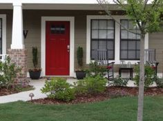 red paint on front door on a taupe vinyl siding house