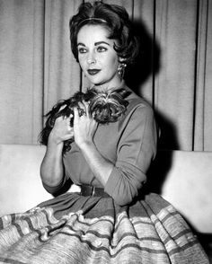 Elizabeth Taylor and Theresa, her Yorkshire terrier, arrive at International Airport (now John F. Kennedy International Airport) after a European tour with Liz's showman husband Mike Todd in 1958.