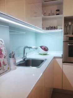 """Antes y Después: cocina en Caballito  Se revistieron las paredes bajo las alacenas con vidrio blanco """"Crisarte"""" y se colocaron perfiles de iluminación led de Voir."""