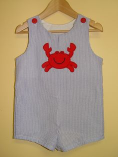 Your little boy will wear this all shortall all summer long. Our tab-back shortall features red button tabs and long straps that allow room to grow. Navy and white seersucker with a crab appliqué. Fit is true to size. Was: $59 Now: $28 (appliqué & shipping included). Sizes: 6m, 9m, 12m, 18m, 24m, 3, 4 & 5. Shop Just Ducky's Flash Sales now!