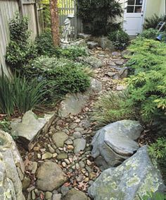 A dry streambed—one that has water running in it only in wet weather—can secure the soil and direct rainwater runoff while turning an eyesore into an appealing garden feature