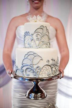 Pretty and delicate. I love the tall top layer. (She is making me nervous holding this cake though)