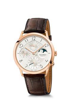 """Bei der anderen großen Neuheit von Hermès, der """"Slim d'Hermès Quantieme Perpetual"""" merkt man sofort, dass der Kreativdirektor sowohl Uhrmacher als auch Industriedesigner ist. Fast vier Jahre lang ließ man sich Zeit, aus der fast 90-jährigen Uhrmachertradition des Hauses, eine vollkommen neue Uhrenlinie zu entwickeln. Eigens für die Ziffern engagierte man den Graphiker Philippe Apeloig, der die berühmten Poster für Reitturniere entwarf. Das speziell für diese Uhr gebaute und finissierte Werk…"""