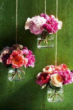 Frascos con flores colgados con soguilla