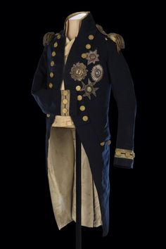 Nelson's Trafalgar coat.Royal Naval uniform: pattern 1795-1812 (Nelson's Trafalgar coat). Made before 1805. England. Materials brass; gold alloy; metal thread; silk & wool. Vice-admiral's undress coat worn by Nelson (1758-1805) at the Battle of Trafalgar. There is a bullet hole on the left shoulder, close to the epaulette. The damage to the epaulette itself is also apparent. There are blood stains on tails and left sleeve-more info here
