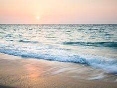 Fototapete Wellen brechen am Strand im Abendrot