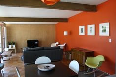 Gorgeous mid-century living room. Love the orange accent wall color.