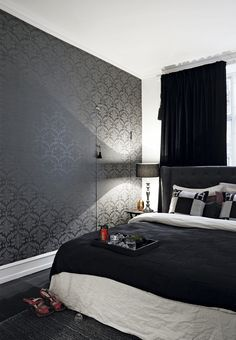 Modern bedroom with a Hästens bed, elegant patterned wallpaper and heavy velvet curtains.