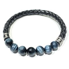 """Natural Stone & Woven Leather Men's Bracelet $220.00 Harness nature's power with this hand woven leather bracelet featuring polished semi-precious gemstone beads. Four bead options available: Yellow tiger's eye, blue tiger's eye, conch shell, and onyx. Mix and match bracelets for a bolder look."""