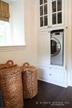 In a master bedroom's walk-in closet, hides a combination washer and dryer unit in a cabinet.