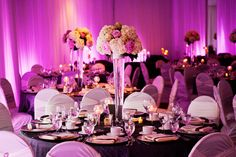 Pink and Grey wedding decor. Tall Centerpieces with cream hydrengea, pink peonies, & roses. Ivory gisselle chair covers, SIlver charger plates, and charcoal grey crinkle table linens. Wall draping with pink wall lighting (wall washes) highlightes with sparkling candlelight.