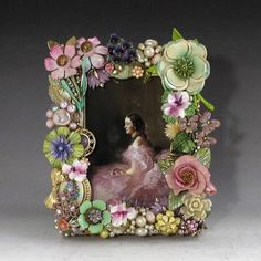 This sweet handcrafted frame is composed of vintage costume jewelry-most of which dates from the mid-20th century. Find many enamel on metal flowers, ceramic flowers, several pieces of Royal Adderley English bone china flowers, painted cameo, rhinestones and pearls. The frame is wood