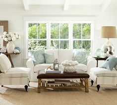 Pretty white and light blue living room with natural textures and big windows