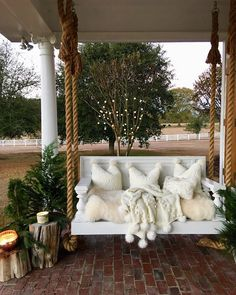 Porch with rope swing decorated with white faux fur cushion, throw pillows and Anthropologie throw. It looks like a fluffy cloud! More on Home Bunch blog