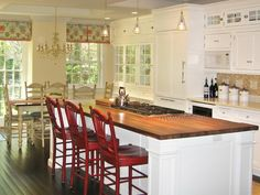Kitchen Island w/ Red Chairs - love the glass doors on the hutch!