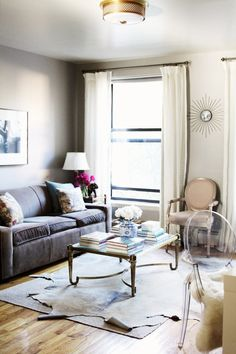 I love this NYC living room. Mitchell Gold + Bob Williams sofa, french brass coffee table eBay find and my favorite element: a layered neutral-colored cowhide on top of a sisal rug to creates texture