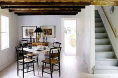 Rustic wood beams provide a stark contrast to the white walls and sleek furniture