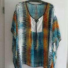 Geometric print tunic Bright colors in a cool print of blues, orange, rust & white.  Placket in front has beaded tie and white lace.  Polyester, batwing style,,best with camisole or tube top underneath. NY Collection Tops