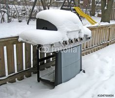 A backyard barbecue covered in snow.