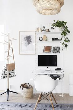 Gorgeous working space- plenty of white mixed with green plants, a woven light fixture, and black and white accents.