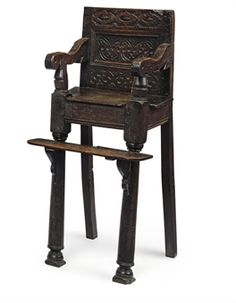 A CHARLES I OAK CHILD'S HIGH CHAIR  CIRCA 1640  With footrest supported on scroll brackets, the crest carved with strapwork, the panel with interlocking motif  33½ in. (85 cm.) high